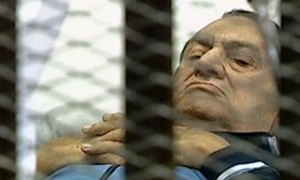 Former Egyptian president Hosni Mubarak lying on a stretcher inside a cell in a courtroom in Cairo. Photograph: AFP/Getty Images