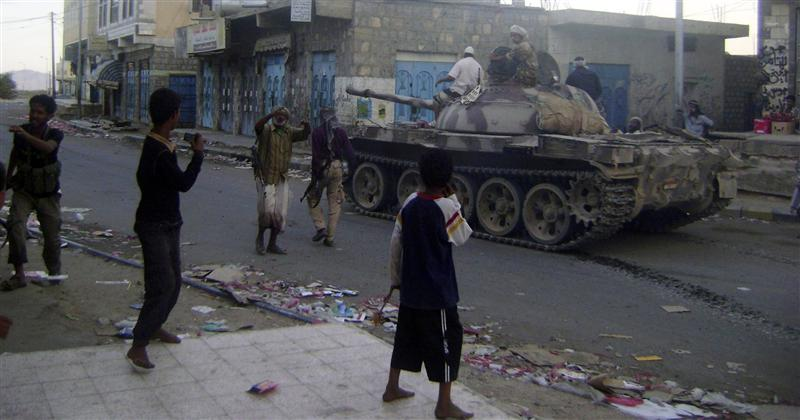 Boys watch an army tank on a street in the southern Yemeni town of Lawdar