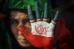 A supporter of Iranian President Mahmoud Ahmadinejad displays her hand painted with the Iranian flag, also used as a sign for his party, at his final election campaign rally, on Azadi street in western Tehran, Iran, Wednesday, June 10, 2009. (AP Photo/Ben Curtis)