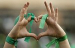 A supporter of reformist candidate Mir Hossein Mousavi forms a heart shape with her hands, while wearing green ribbons - the color of the party, amidst a festive atmosphere at an election rally rally in Tehran, Iran, Tuesday, June 9, 2009. (AP Photo/Ben Curtis)