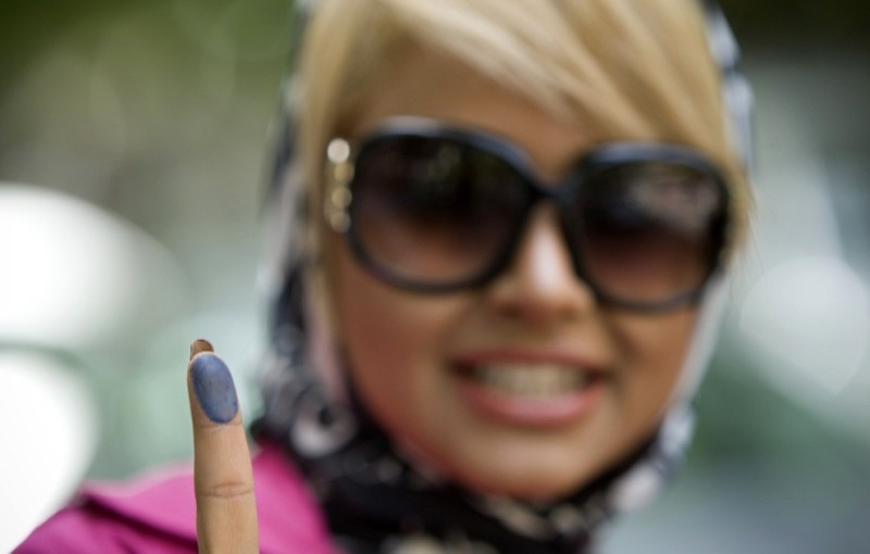 A woman shows the ink on her finger after casting her ballot for the Iranian presidential election in Tehran June 12, 2009. (REUTERS/Caren Firouz)