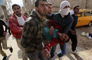 Stone-throwing Palestinian protesters carry an injured protester during clashes with Israeli security officers in the West Bank village of Tamoun, near the West Bank city of Jenin January 1, 2013. Clashes broke out after an Israeli military operation in the village on Tuesday. REUTERS/Ammar Awad