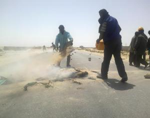 22 Apr 13 Strike leaders extinguish burning tyre