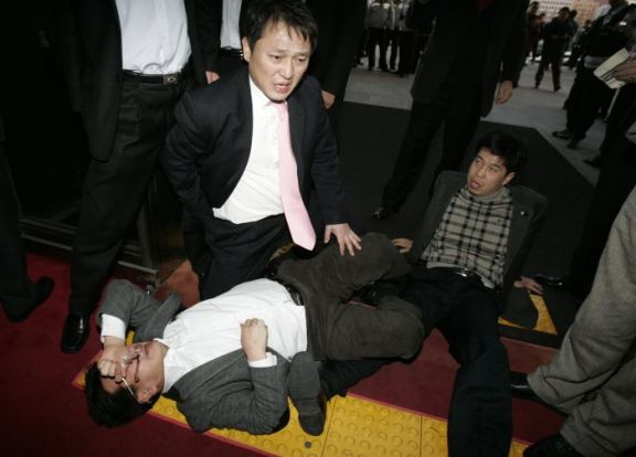 Lawmakers of the main opposition Democratic Party react as they fall down during scuffles with parliament security guards in Seoul